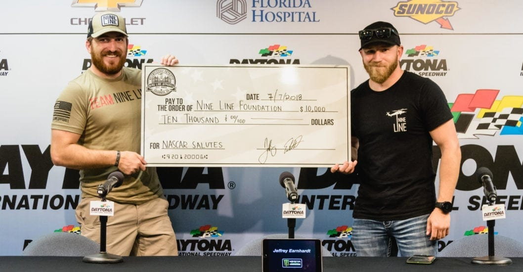 Nine Line CEO Tyler Merritt and Jeffrey Earnhardt with a check for the Nine Line Fountation